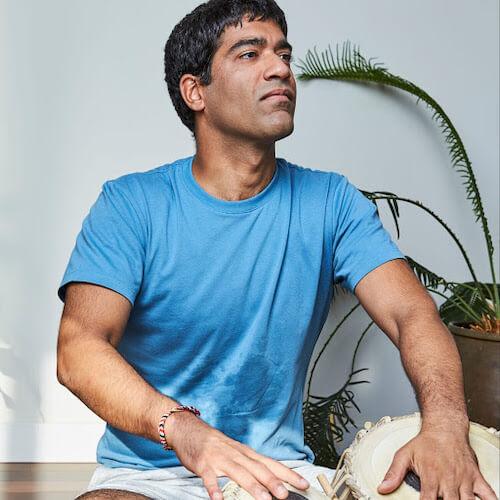Neil Wadhawan, yoga teacher, playing Indian tabla (musical instrument)