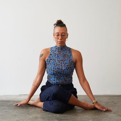 Europa Grace, yoga and meditation instructor, seated in Gomukhasana (Cow Face Pose, and meditating