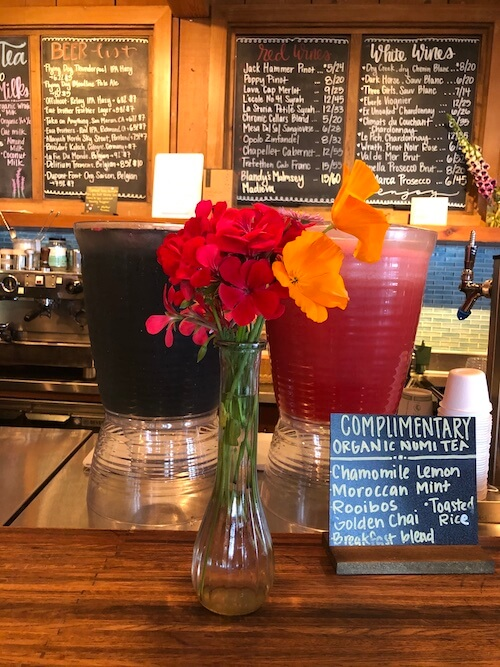 The beverage bar at Esalen, showing a menu of drinks that includes complimentary NUMI teas, a selection of wine and beer, and specialty drinks.
