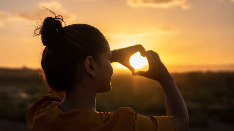 Photo of a person outdoors during sunset, holding their hands in a heart shape.