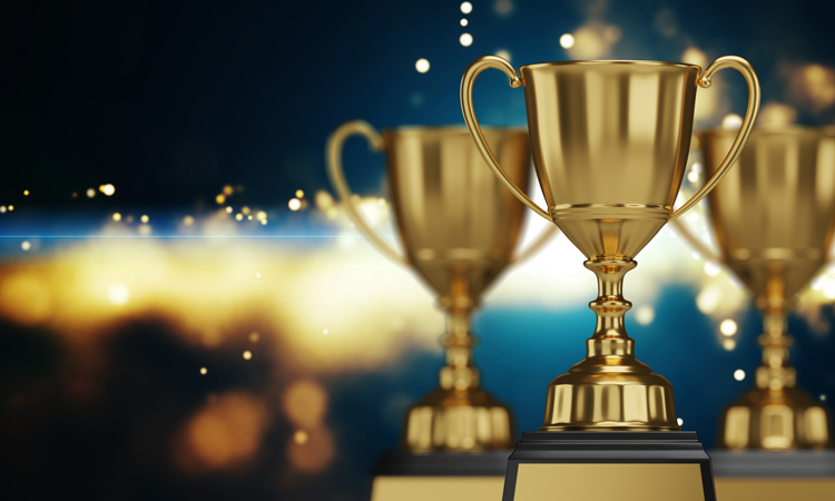 Three gold trophies on abstract background.