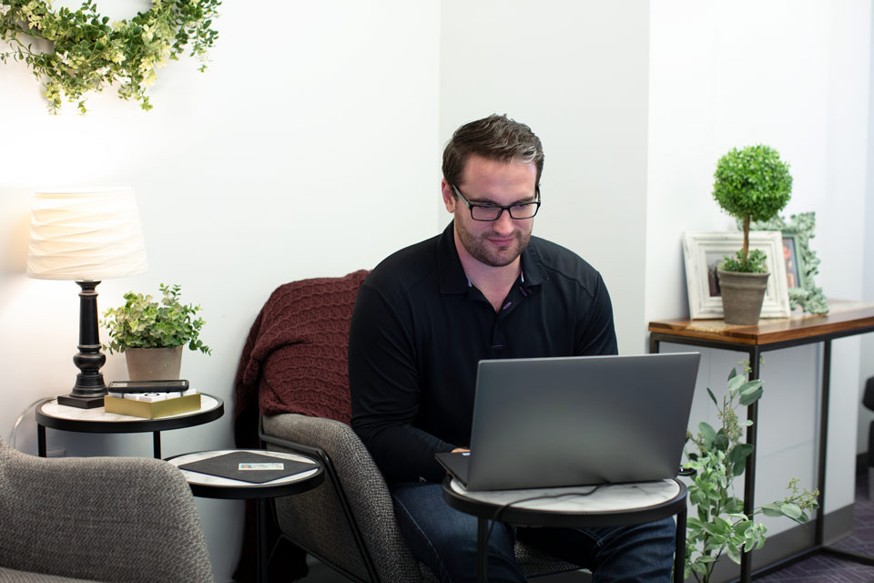 Man in casual home setting completing Remote Online Notarization on laptop computer.