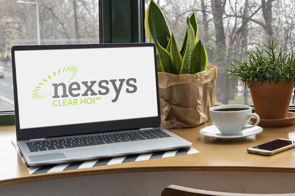 Nexsys Clear HOI logo displaying on the monitor of a laptop on a desk with potted plants.