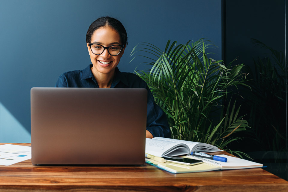 Woman in home office setting with potted plants working on laptop computer.