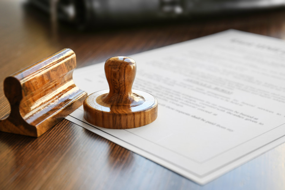Wooden ink and stamp resting on legal documents.