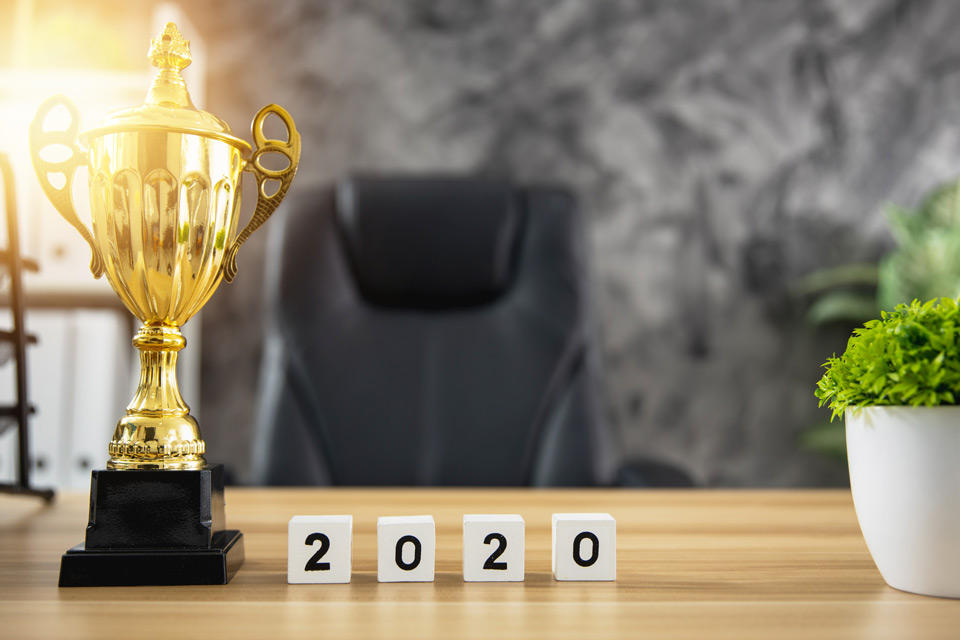"""Trophy on a desk with cubes that spell out """"2020"""" on them."""