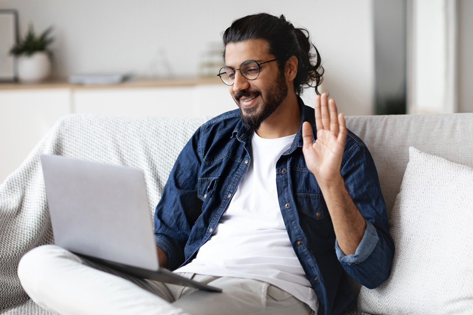 bearded man sitting on couch with laptop raising his hand to identify himself