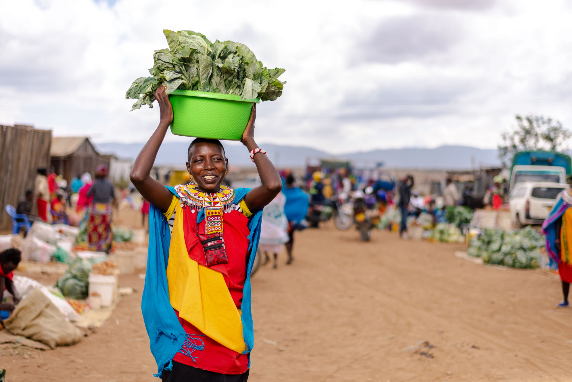 A woman in Kenya holding a basket of vegetables.