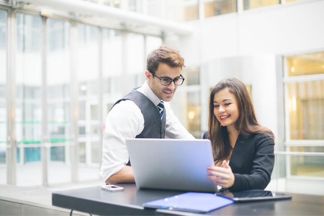 dos colegas trabajando en la computadora portátil