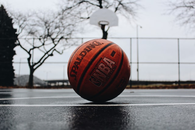 basketball on the ground in a court by the net