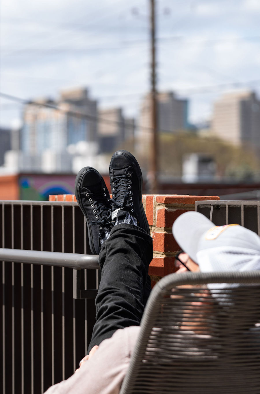 Man in hat with feet propped up on balcony railing enjoys Atlanta skyline from Local's offices