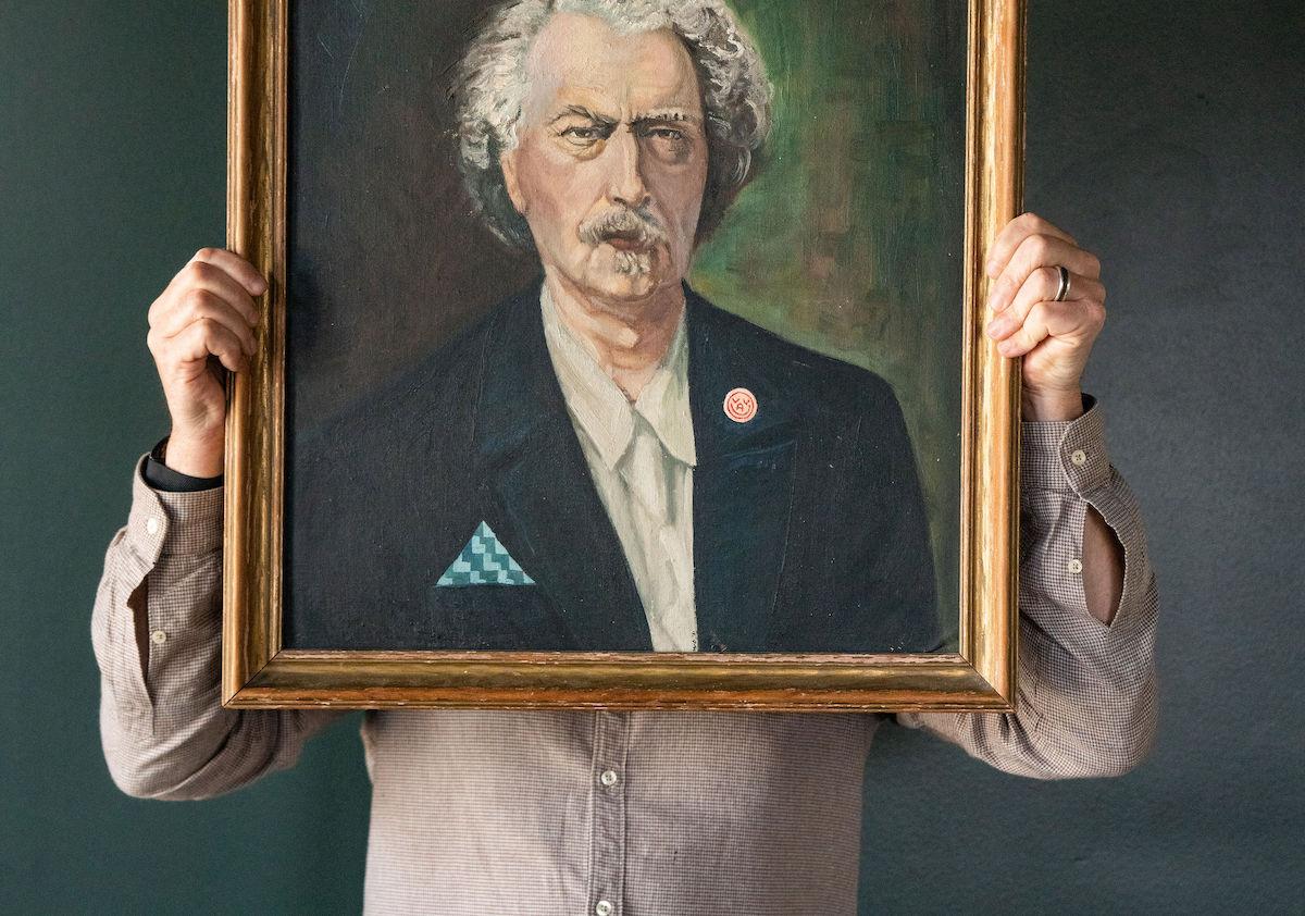 Man holds up oil painting of grumpy patron saint
