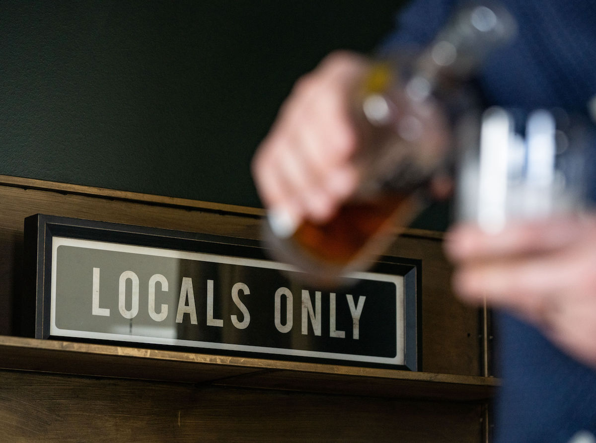 """Man pours glass of whiskey in front of """"Locals Only"""" sign"""