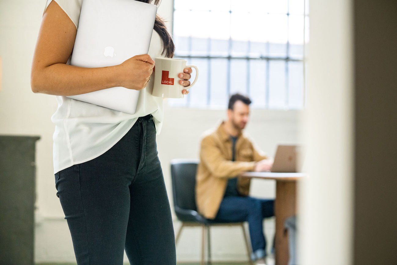 Lady carries Local-branded mug and laptop through office as man works from wooden table under large industrial window in the background