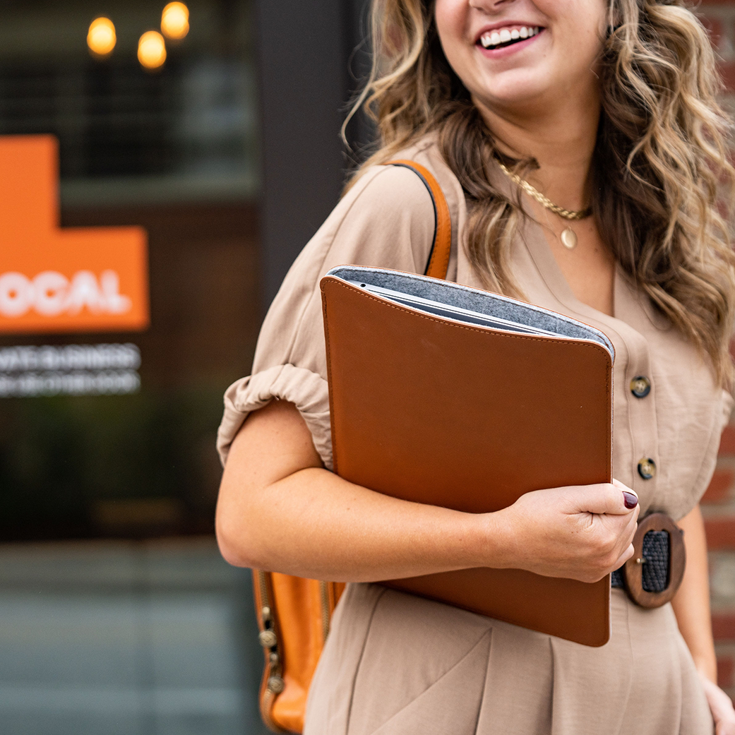 Smiling lady walks with laptop in front of Local's office