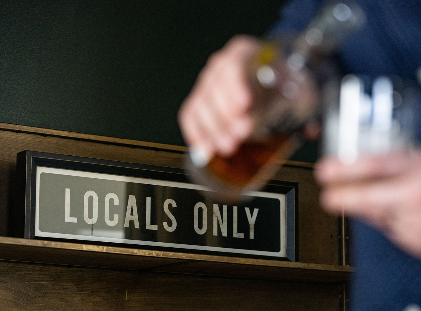 """Man pours glass of bourbon in front of """"Locals Only"""" sign"""