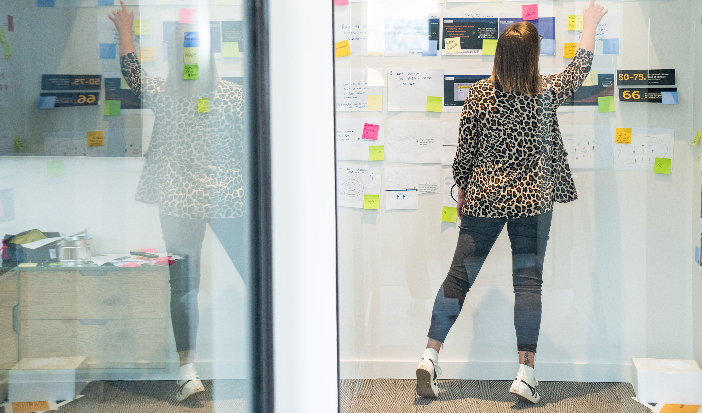 Lady in conference room points to sticky note on brainstorm wall covered in printouts and photos
