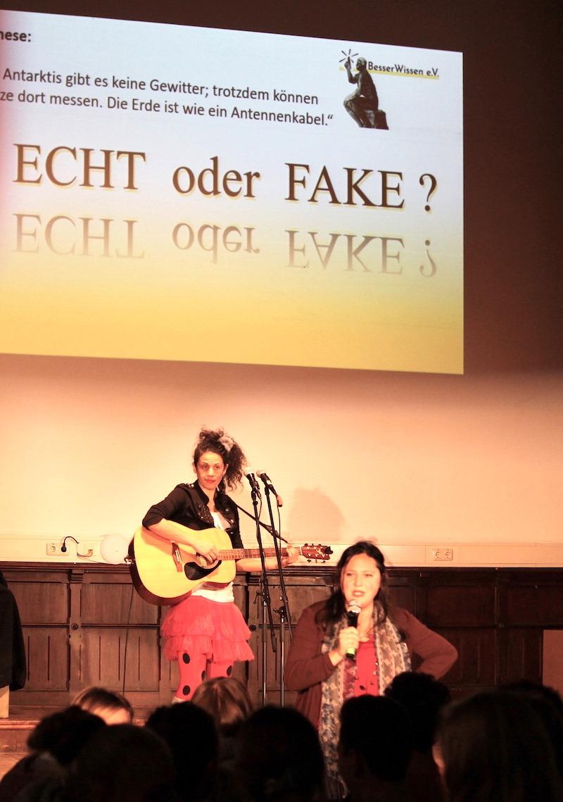 """Foto von zwei Refernt*innen auf der Bühne im Hintergund Präsentation an der Wand mit dem Titel """" Echt oder Fake""""?"""
