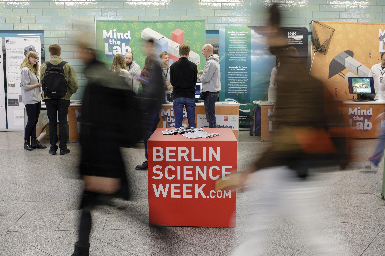 Fotografie mit rotem Kubus im Zentrum des Bilder mit Aufschrift Berlin Science Week, umgeben von verschwommenen Personen
