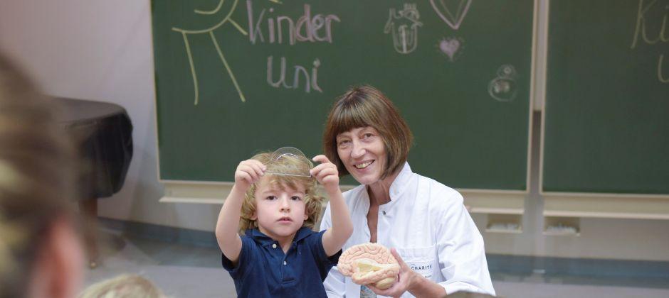 """Foto von Ärztin und Kind vor grüner Tafel mit der Aufschrift """"KinderUni"""""""