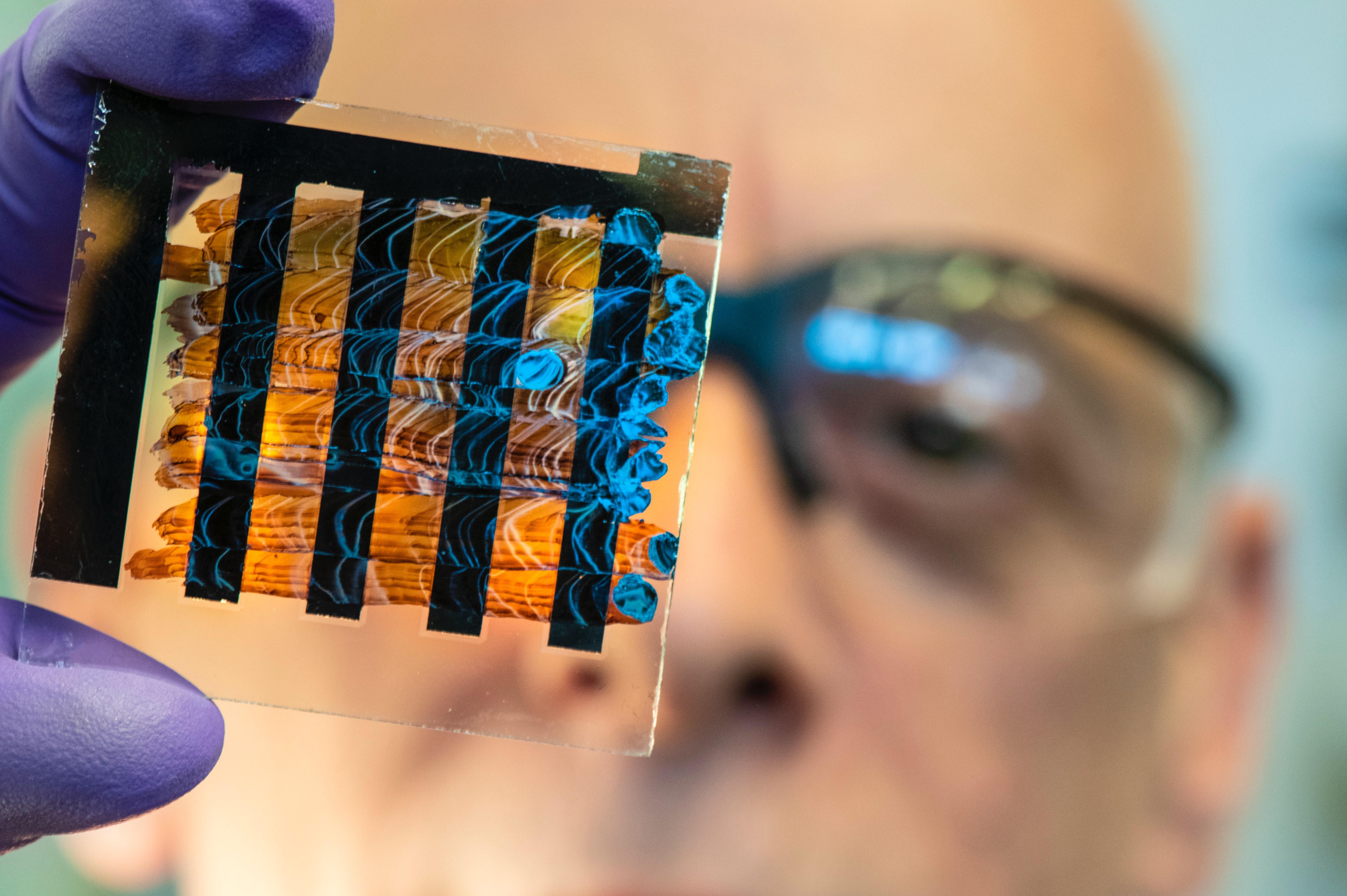 Foto von Mann mit Schutzbrille, der sich eine durchsichtige Glasplatte mit Farbe