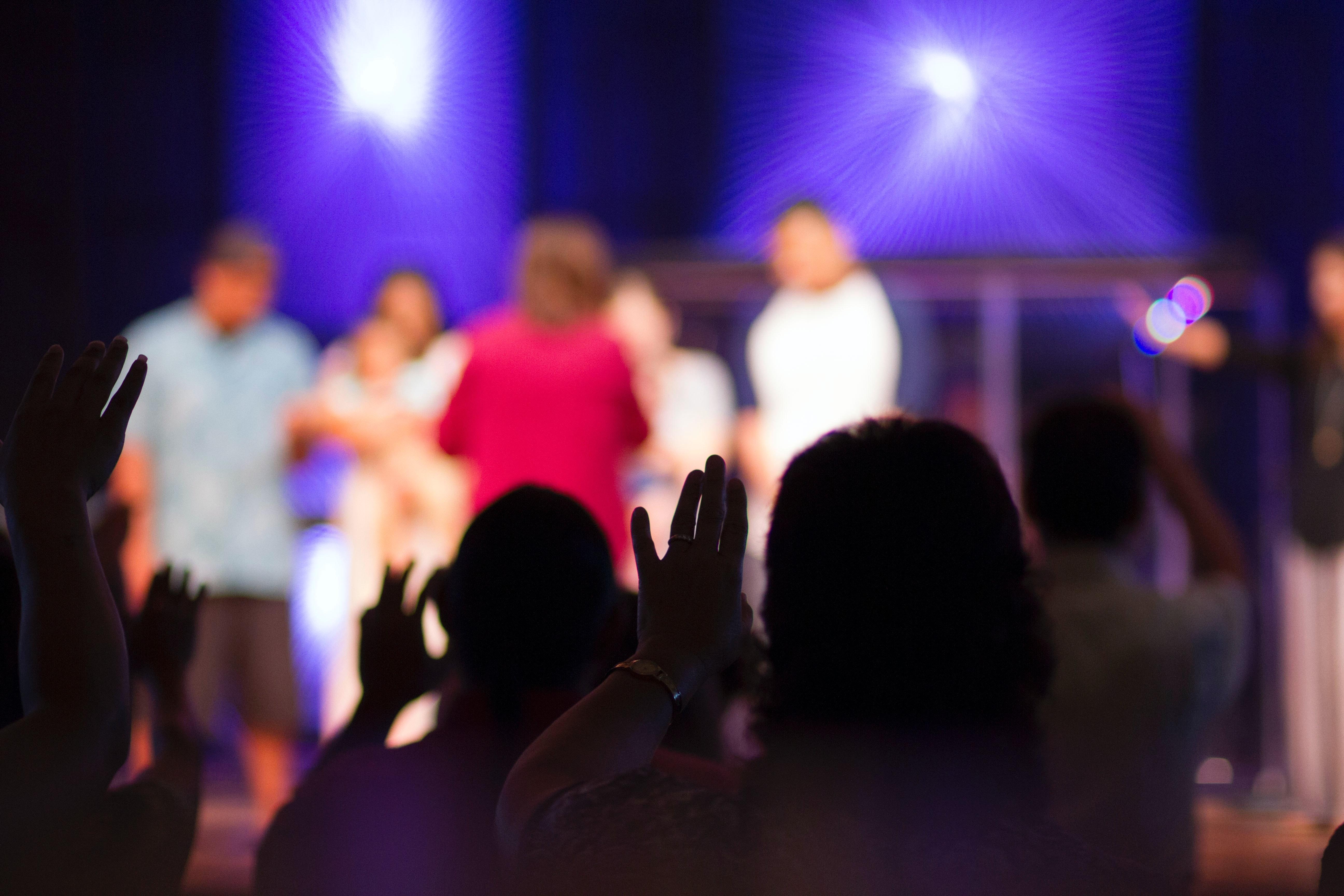 Foto von Menschen auf einer Bühne und davor Publikum