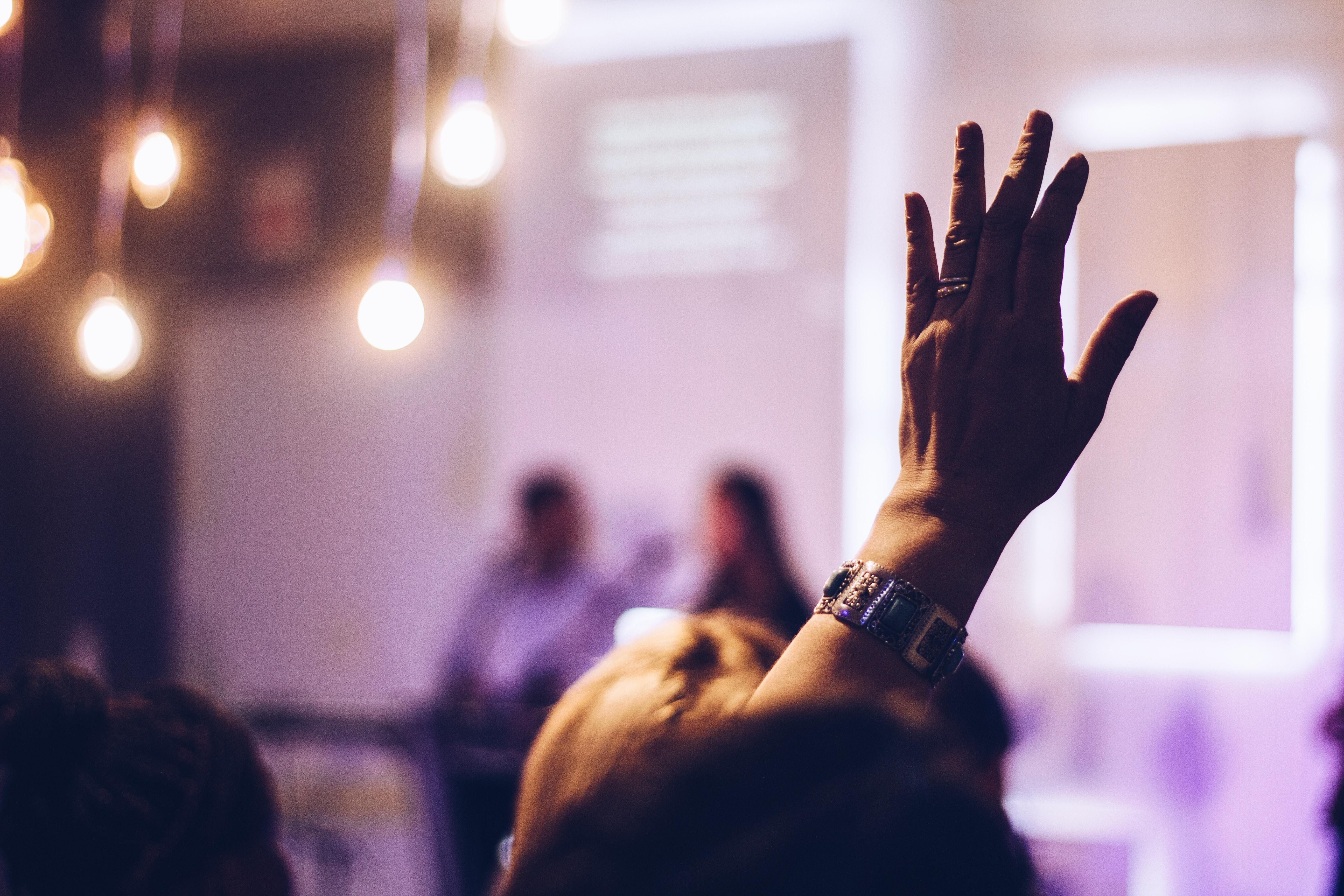Foto von Mensch, der seine Hand zur Frage erhoben hat
