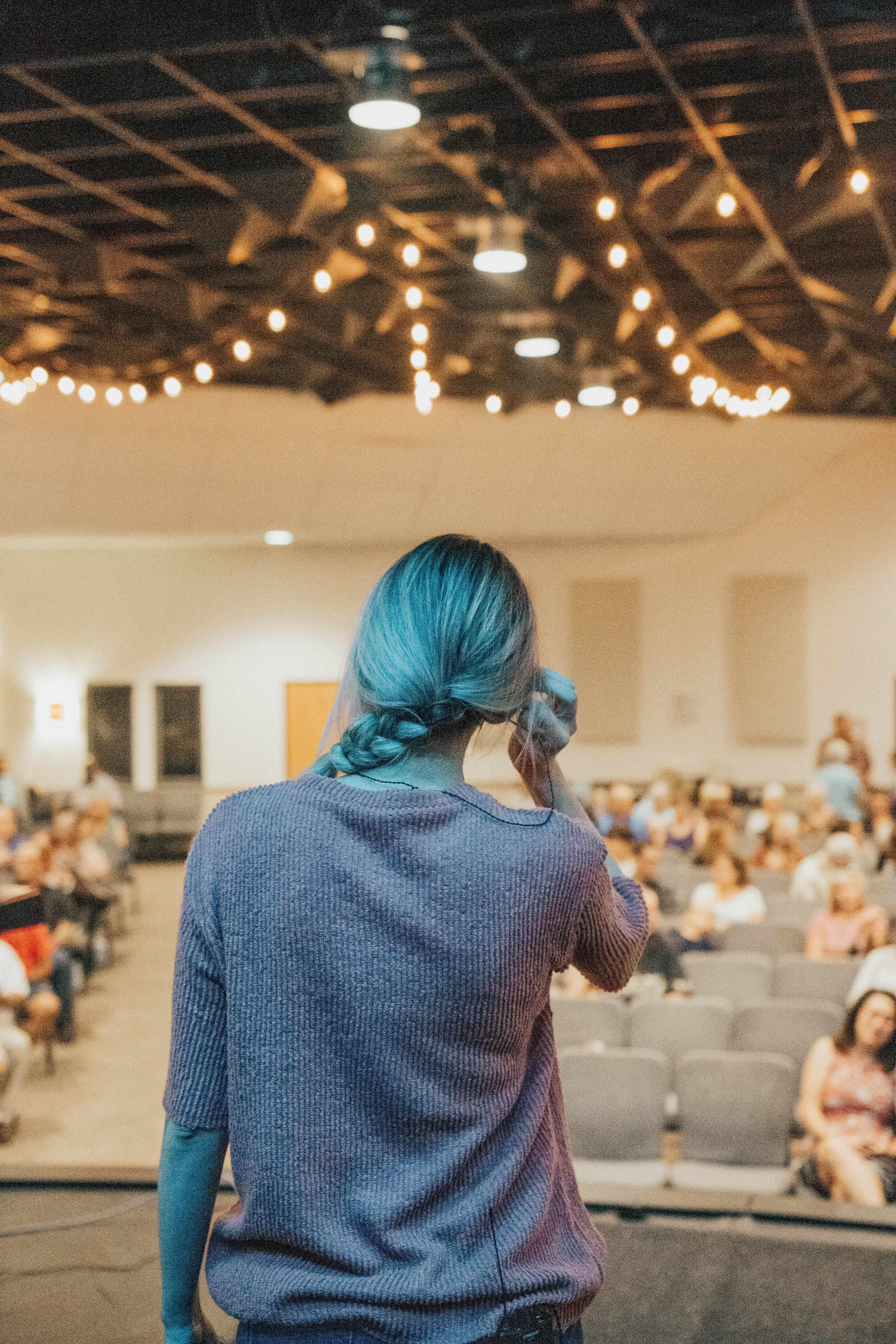 Foto von Vortragender von hinten auf einer Bühne stehend, im Hintergrund verschwommen Zuhörer*innen