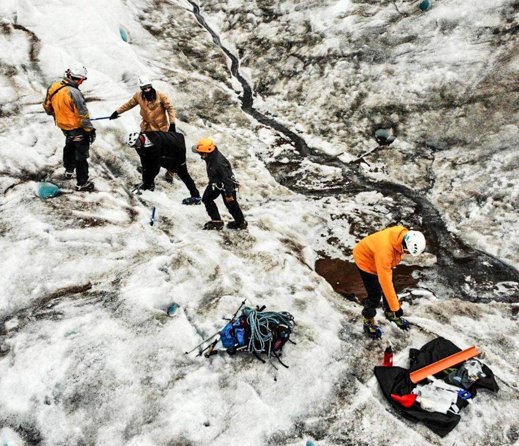 Menschen in Schutzkleidung auf einem Gletscher