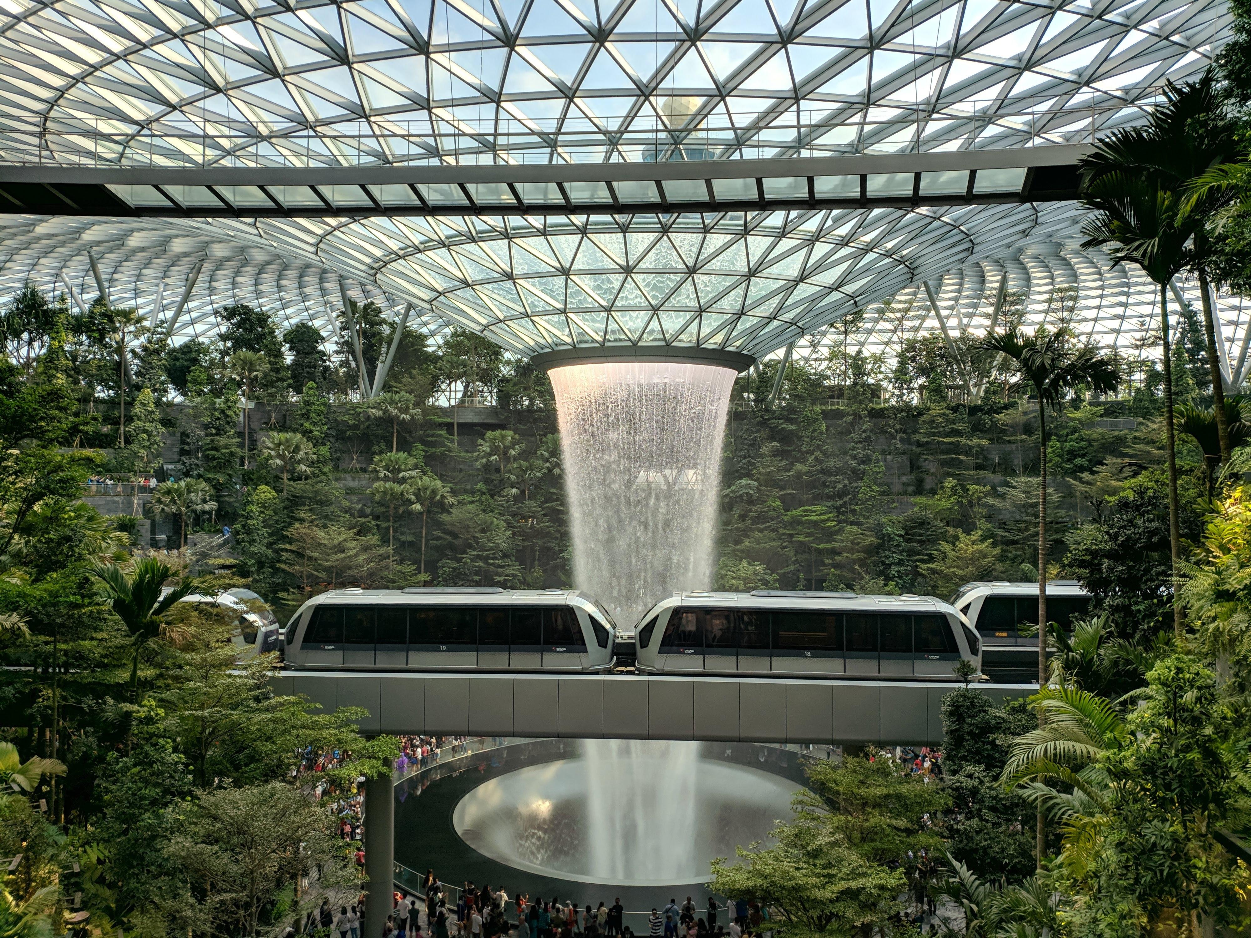 Foto von Wasserfall in einem Gebäude und Straßenbahn über einer Brücke