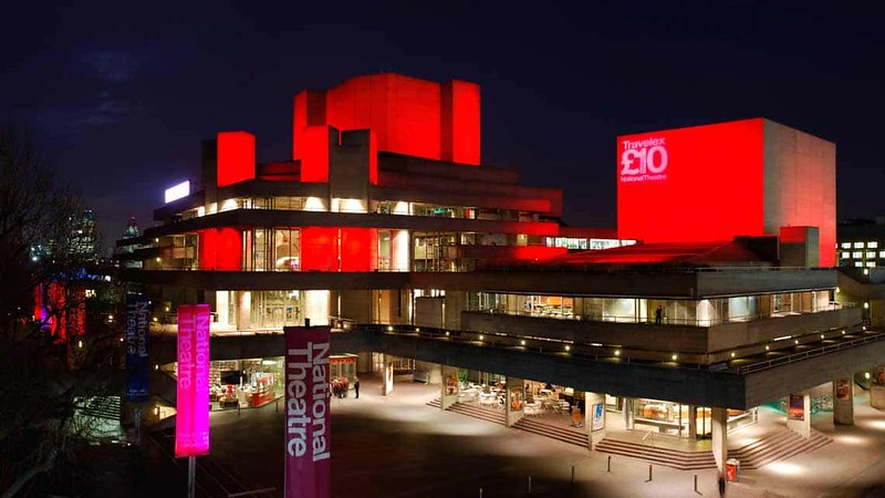 Outside of National Theatre building lit up in red and pink.