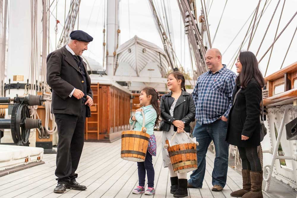 Family of four on the Cutty Sark's deck learning facts from a staff member.