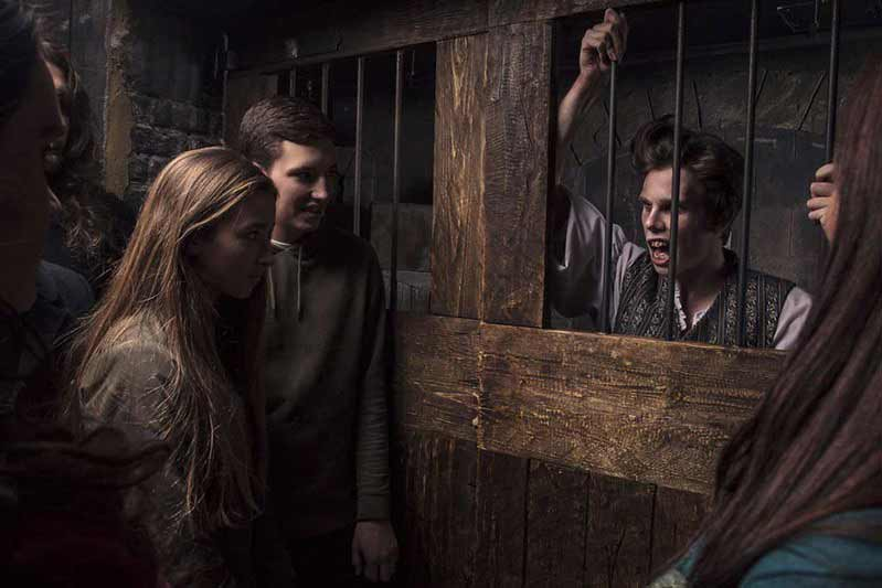 Two innocent bystanders passing a prison cell with a menacing-looking London Dungeon character inside.