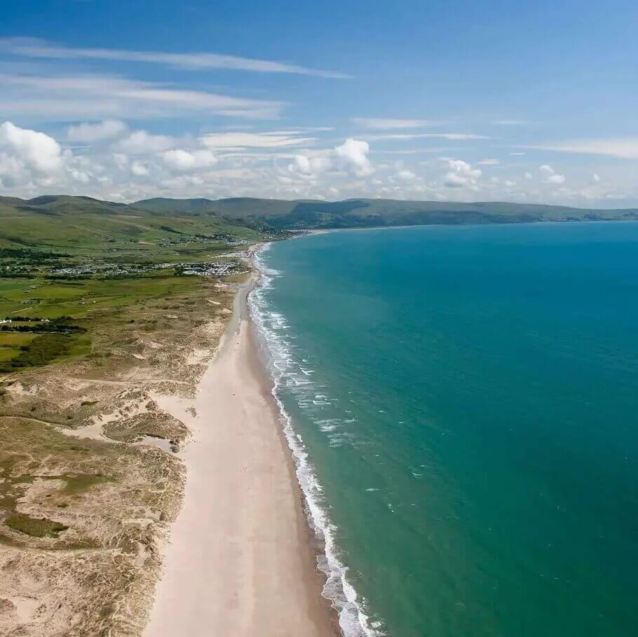 The coastline at Traeth Abermaw Beach (Barmouth Beach) with a white beach and blue ocean.