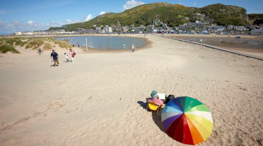 Traeth Abermaw Beach (Barmouth Beach), on a summer's day with a colourful rainbow umbrella on the sand.