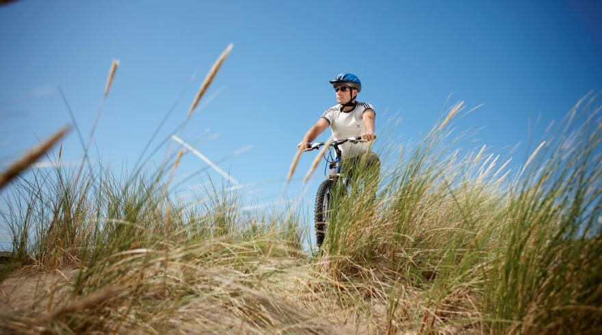 A cyclist ready to cross the dunes at Traeth Abermaw Beach (Barmouth Beach), against a blue sky with grass and sand in the foreground.