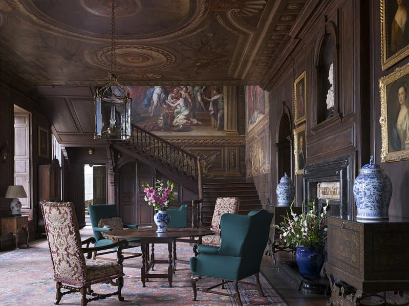 A table and four chairs and an impressive wall and ceiling painting in Hanbury Hall.