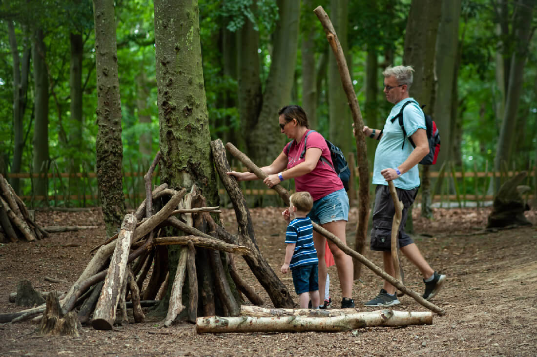 A family building a den from wooden sticks in the forest at BeWILDerwood.