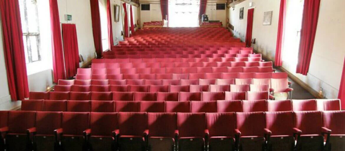 An inside view of the theatre at St George's Guildhall with lots of red chairs.
