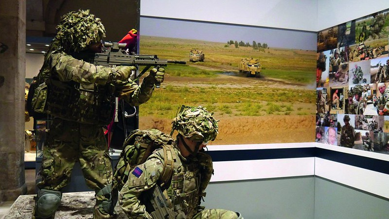 Two modern soldiers, one crouching, one with gun at Household Cavalry Museum.