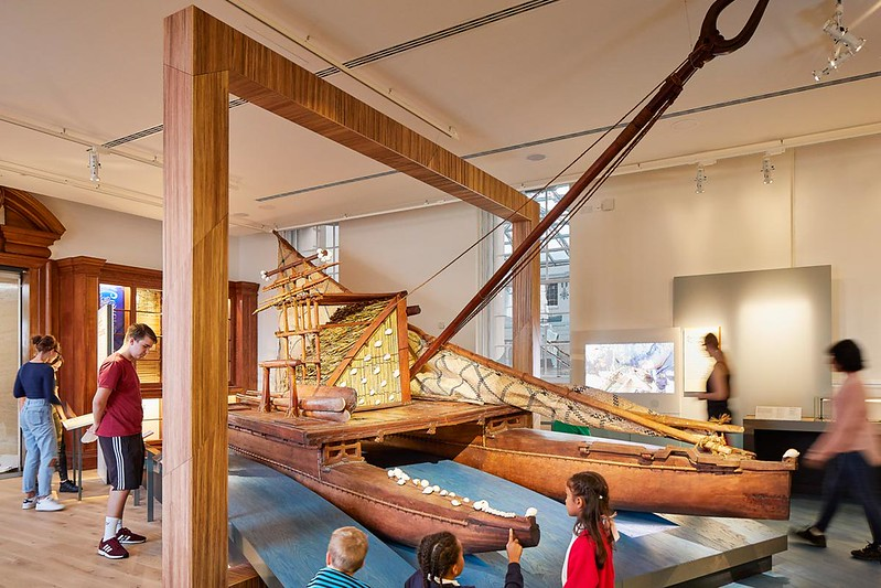 Families observing model boat at Pacific display at National Maritime Museum.