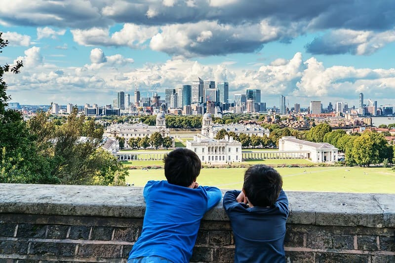 Two children looking at the view of the Queen's House in Greenwich with the City of London in the background.