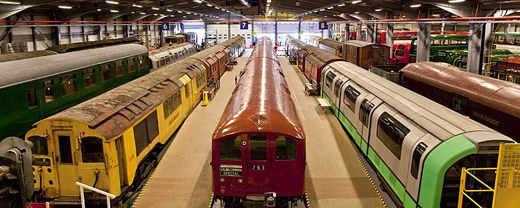 Three different coloured Underground trains displayed at the London Transport Museum Depot.