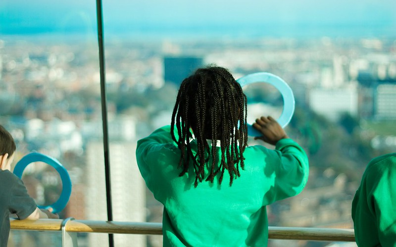 A young boy looking out through a porthole at the Spinnaker Tower.