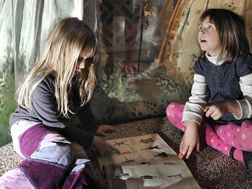 Two young girls sat on the floor learning at the Museum of London.