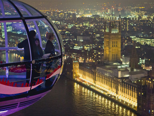 A family looking out at the Houses of Parliament from the London Eye at night.