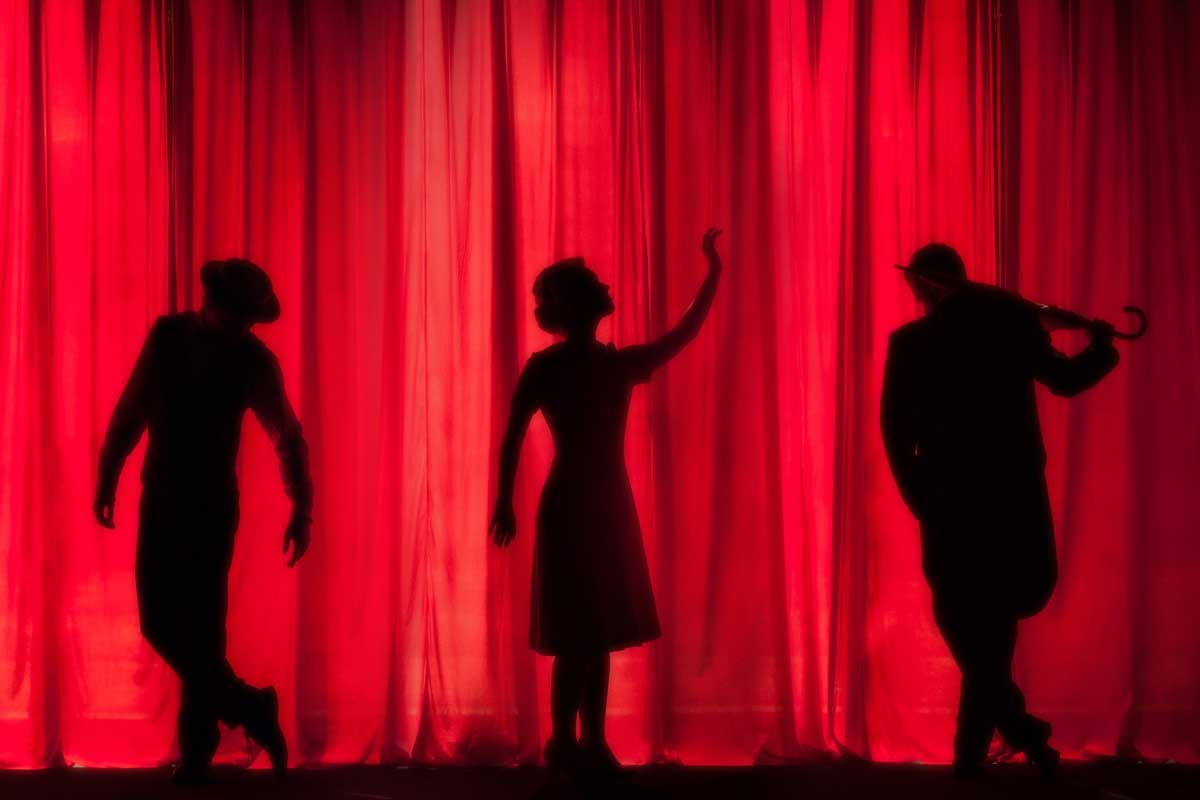 Silhouettes behind red theatre curtain.