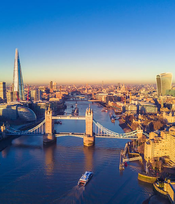 View of London across the River Thames featuring Tower Bridge and the Shard on a sunny day.