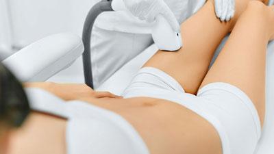 Une femme en train de se faire éliminer les poils de la jambe avec de la lumière pulsée intense ou du laser.