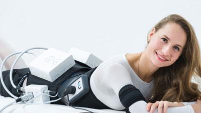 Une femme souriante allongée sur le ventre en pleine séance d'éléctrostimulation musculaire. Des électrodes sont visibles sur la taille, les fesses, les bras et les jambes.